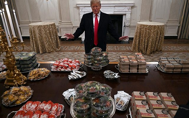 US President Donald Trump talks to the media about the table full of fast food in the State Dining Room of the White House in Washington on Jan. 14, 2019, for the reception for the Clemson Tigers. (AP Photo/Susan Walsh)