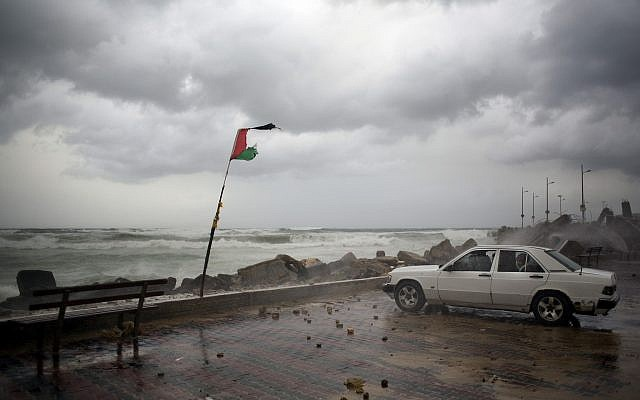 A Palestinian family sits inside their car on the Mediterranean seaside during a rain storm in Gaza City, Wednesday, Jan. 16, 2019. (AP Photo/Khalil Hamra)