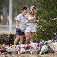 Two women stand at a floral tribute, Friday, Jan. 18, 2019, at the scene where the body of Israeli student Aiia Maasarwe was found earlier in the week in Melbourne, Australia.(Ellen Smith/AAP Image via AP)