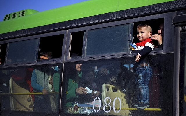 A refugee child looks out of a bus window that will take him home to Syria, in the northern Beirut suburb of Burj Hammoud, Lebanon, January 24, 2019. (AP Photo/Bilal Hussein)