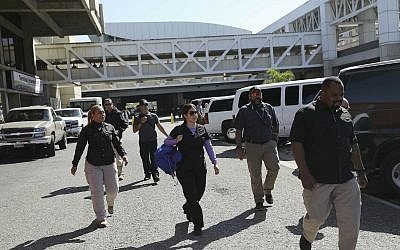United States embassy security agents walk after dropping off US embassy employees and their families at the Simon Bolivar international airport in La Guaira, Venezuela, Friday, Jan. 25, 2018. (AP/Rodrigo Abd)