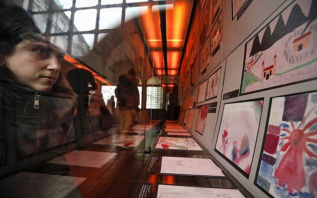 A visitor looks at the collection of drawings at the Jewish Museum in Prague, Czech Republic, Jan. 24, 2019, made by Jewish children who passed through the Terezin Ghetto during WWII (AP Photo/Petr David Josek)