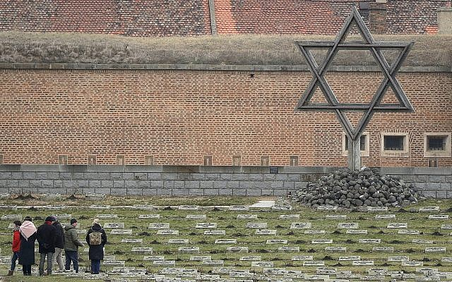 Visitors walk through the cemetery of the former Nazi concentration camp in Terezin, Czech Republic, Jan. 24, 2019  (AP Photo/Petr David Josek)
