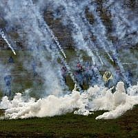 Tear gas canisters are fired by Israeli troops at Palestinians during clashes with Palestinians after the funeral of Hamdi Na'asan in the village of Mughayyir near the West Bank city of Ramallah, January 27, 2018 (AP Photo/Majdi Mohammed)