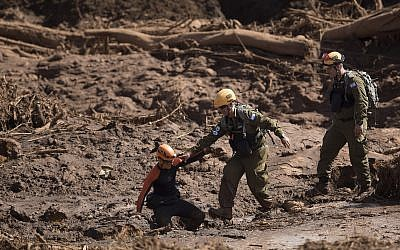 A Brazilian firefighter, left, helps an Israeli rescue specialist to cross a muddy area as they arrive at a site where a person found dead person inside a vehicle stuck in the mud, days after a dam collapse in Brumadinho, Brazil, Monday, Jan. 28, 2019. (AP/Leo Correa)