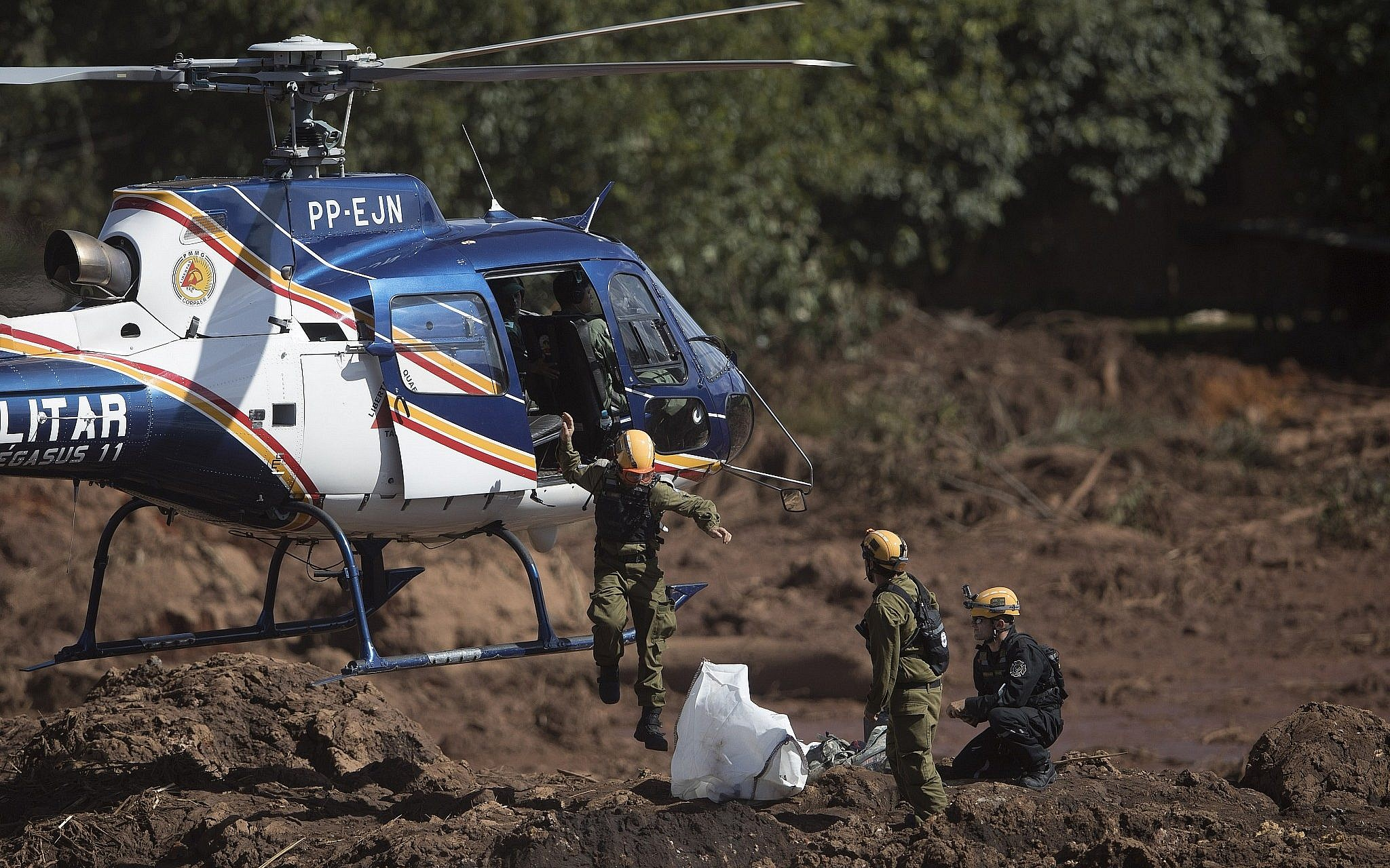 Israeli rescue specialists arrive at a site where a body was found inside a vehicle stuck in the mud days after a dam collapse in Brumadinho Brazil