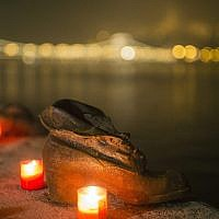 Candles burn in front of the cast iron shoes at the Holocaust Memorial on the quay of the River Danube, during International Holocaust Remembrance Day in Budapest, Hungary, Wednesday, Jan. 27, 2016 (Balazs Mohai/MTI via AP)