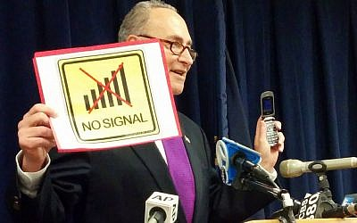 """With a  flip phone in one hand, and a """"no signal"""" sign in the other, Sen. Charles Schumer speaks about improving New Yorkers' cellphone service  by tracking dead zones where calls are regularly dropped, in New York, Sunday, Jan. 17, 2016. (AP Photo/Julie Walker)"""