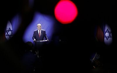 In this photo taken with a red television camera control light in the foreground, Prime Minister Benjamin Netanyahu attends a news conference with German Chancellor Angela Merkel during a meeting at the chancellery in Berlin,  October 21, 2015. (AP/Markus Schreiber)