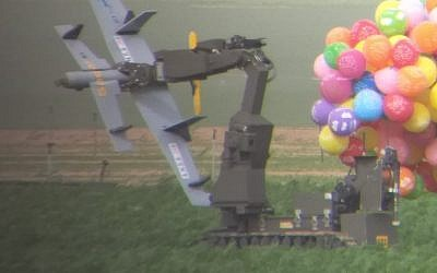 A police bomb disposal robot carries away a drone-shaped device from the Gaza Strip, borne by dozens of helium balloons, which landed in a carrot field in southern Israel on January 6 ,2019. (Israel Police)