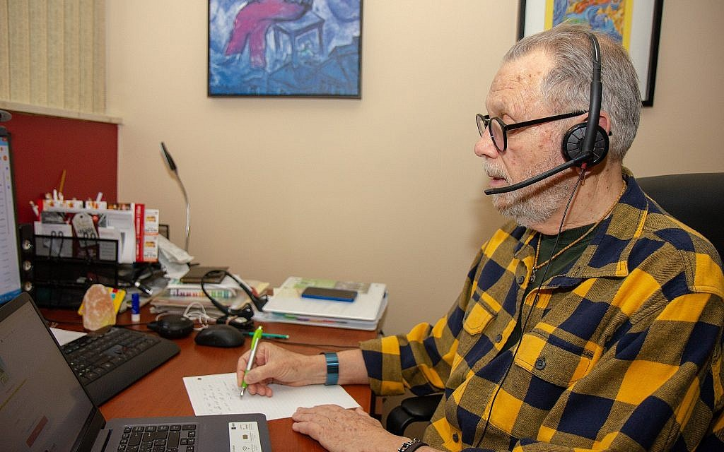 ERAN volunteer Arie Eigner in his apartment, where he receives calls on his laptop. Volunteers take notes during calls for report they must prepare after each call, which they send to their supervisor in Israel. (Etye Sarner)
