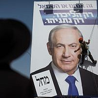 An ultra-Orthodox man looks at workers hang a Likud campaign poster of Prime Minister Benjamin Netanyahu at the entrance to Jerusalem on March 11, 2015 in Jerusalem. (Yonatan Sindel/FLASh90)