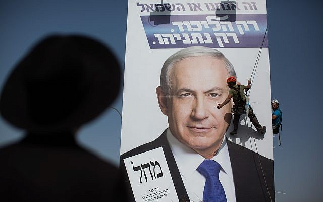 An ultra-Orthodox man looks on, as workers hang a Likud campaign poster featuring Prime Minister Benjamin Netanyahu at the entrance to Jerusalem on March 11, 2015. (Yonatan Sindel/Flash90/File)