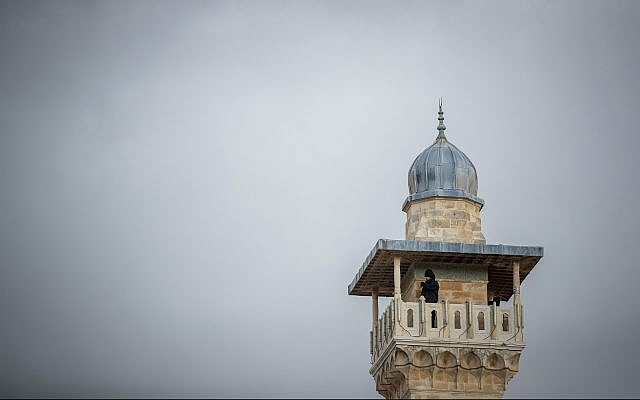 A man looks out from a minaret at the Al-Aqsa Mosque in the Old City of Jerusalem on January 23, 2018. (Yonatan Sindel/Flash90)