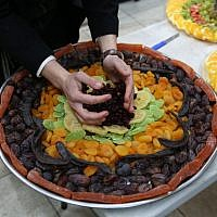 Ultra-Orthodox Jews prepare a platter for a Tu B'Shvat seder in the northern town of Meron on January 30, 2018. (David Cohen/ Flash90/ File)