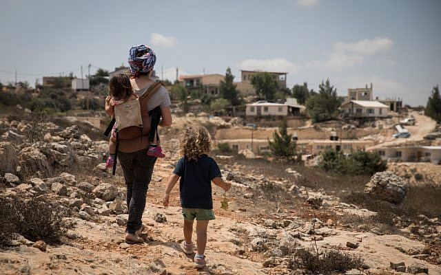 Illustrative: A woman takes her children on a walk in  the Jewish settlement of Sde Boaz in Gush Etzion, West Bank, on August 28, 2018. (Hadas Parush/Flash90)