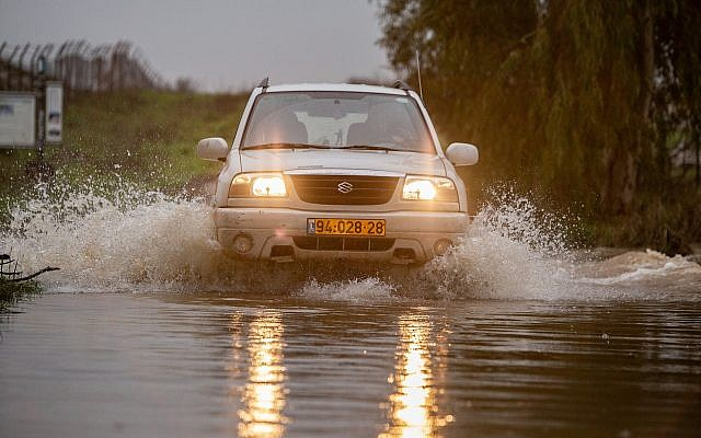 A vehicle crosses a flooded stream on the Golan Heights, January 14, 2019. (Maor Kinsbursky/Flash90)