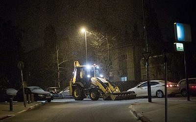 A tractor clears snow from a road as snow falls in the Old Katamon neighborhood in Jerusalem, on January 16, 2019. (Hadas Parush/Flash90)