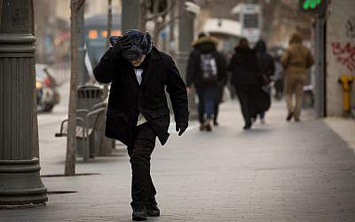 People walk in heavy winds and rain on Jaffa Street in Jerusalem on January 16, 2019. (Yonatan Sindel/Flash90)