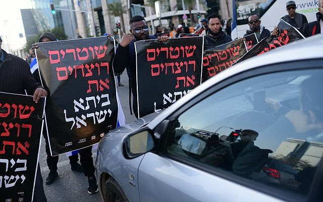 """Ethiopian-Israelis protest police violence in Tel Aviv on January 30, 2019. The signs read, """"Cops are murdering the Beita Israel,"""" the name of the Ethiopian Jewish community. (Tomer Neuberg/Flash90)"""
