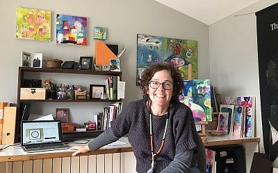 Artist Susie Lubell at her Tsur Hadassah rooftop studio, where she creates collages and ketubot sold on her online stores (Jessica Steinberg/Times of Israel)