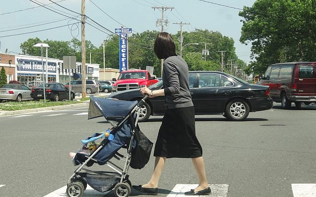 An Orthodox woman pushes a stroller in Lakewood, N.J. in 2013. The population in the largely haredi Orthodox town has boomed in the past couple of decades, and haredi families are looking to move to neighboring towns. (Dennis Fraevich/Flickr via JTA)