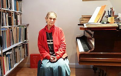 Nelly Ben-Or sitting by one of her two pianos in her London home, December 13, 2018. (Cnaan Liphshiz)