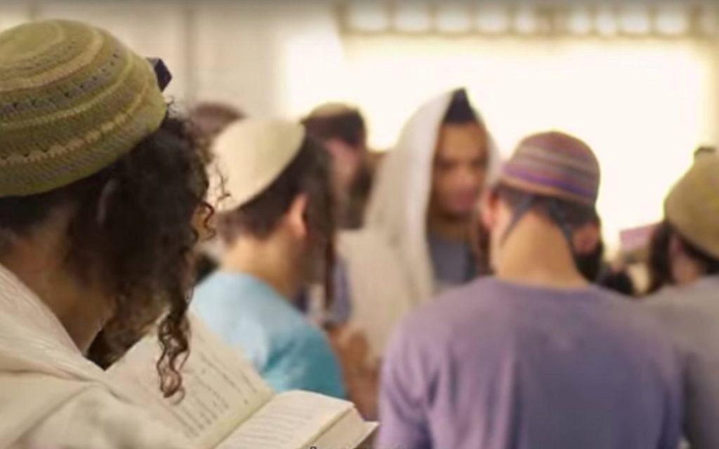 Illustrative: Students pray at the Pri Haaretz yeshiva in the Rehelim settlement. (Screen capture/YouTube)