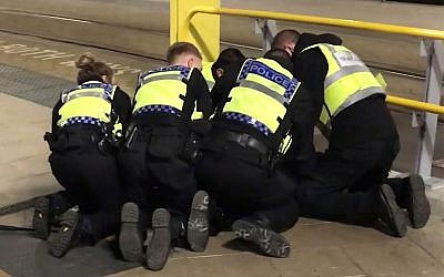 Police restrain a man after he stabbed three people at Victoria Station in Manchester, England, late Monday Dec. 31, 2018. Two commuters - a man and woman in their 50s - were taken to hospital with knife injuries and a British Transport Police (BTP) officer was stabbed in the shoulder. Police said a man was arrested on suspicion of attempted murder and remains in custody. (Sam Clack/PA via AP)