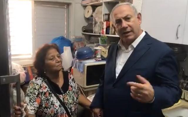Prime Minister Benjamin Netanyahu (R) visiting the home of south Tel Aviv resident Sophia Menashe on August 31, 2017. (Screen capture: Facebook)