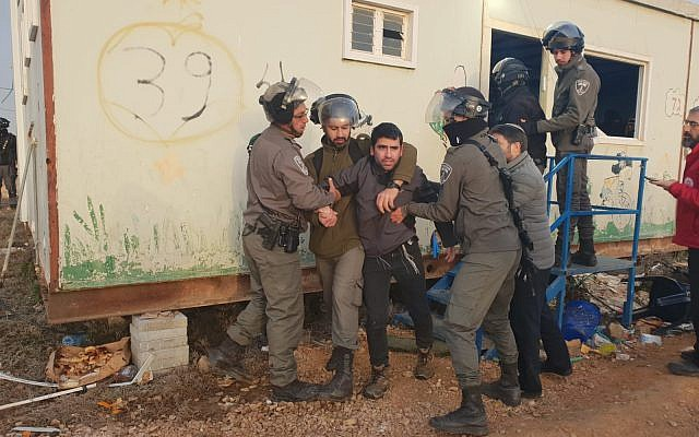 Border Police clear several hundred settler youths who had crammed into a pair of illegally placed mobile homes on the Amona outpost on January 3, 2018. (Binyamin Regional Council)