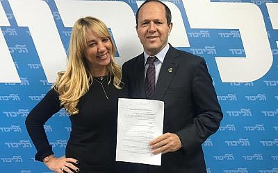 Nir Barkat (R) with an unidentified Likud official after signing his registration form for the Likud party primaries on January 14, 2019. (Courtesy)