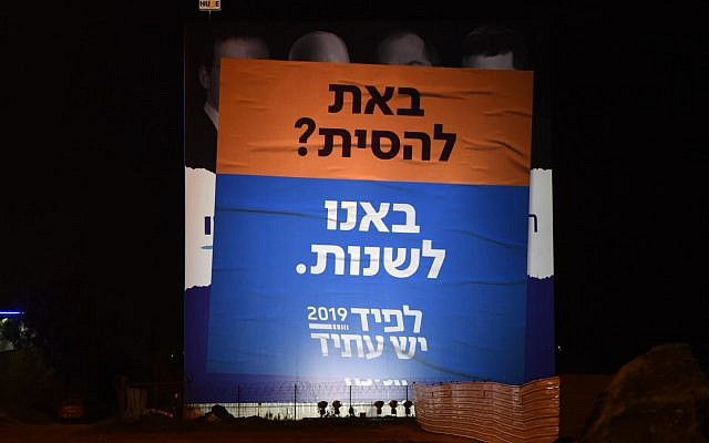 A Yesh Atid election campaign poster at the Glilot junction outside Tel Aviv criticizing 'incitement,' designed to look like it is plastered over a Likud poster attacking journalists, January 25, 2019. (Yesh Atid)