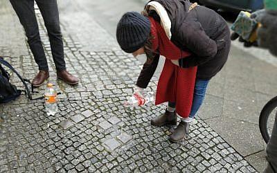 Volunteers clean stolpersteine in Berlin's Kreuzberg neighborhood on international Holocaust Remembrance Day, January 27, 2019. (Yaakov Schwartz/Times of Israel)