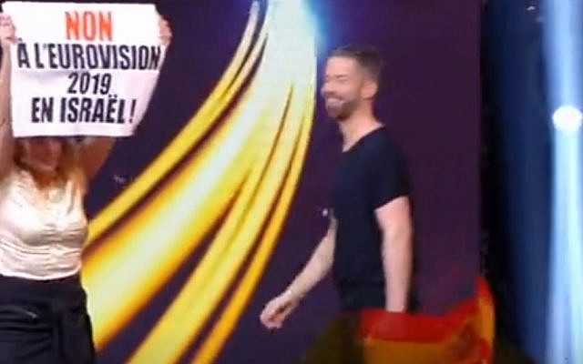 An anti-Israel protester holds a sign during a Eurovision qualifying contest in France on January 19, 2019. (screen capture: Pure Medias)