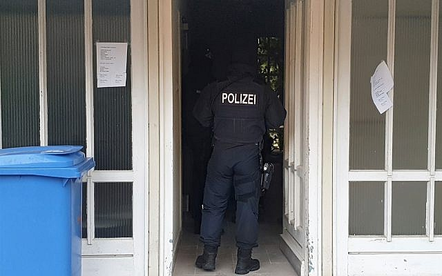 A police officer in an entrance of an apartment building during a raid in the village Meldorf, Germany, January 30, 2019. (Karsten Schroeder/dpa via AP)