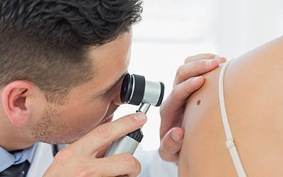 Illustrative image of a dermatologist checking a mole (Wavebreakmedia; iStock by Getty Images)