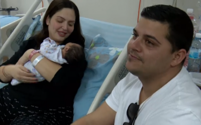 Barak Elimelech (right), his wife Racheli and their newborn (Hadashot news screenshot)