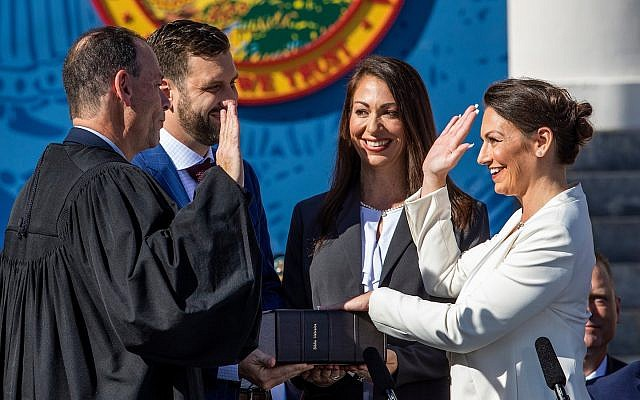 Nikki Fried, right, is sworn in as Florida's commissioner of agriculture on January 8, 2019. Fried's left hand is placed on the first Hebrew Bible published in America. (Photo by Colin Hackley/via RNS)