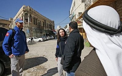 Members of the Temporary International Presence in Hebron (TIPH) talk to local Palestinians as they walk in the West Bank city on January 29, 2019. (Hazem Bader/AFP)