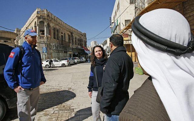 Los miembros de la Presencia Internacional Temporal en Hebrón (TIPH) hablan con los palestinos locales mientras caminan en la ciudad de Cisjordania el 29 de enero de 2019. (Hazem Bader / AFP)