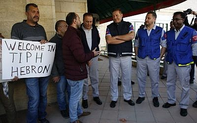 Observers from The Temporary International Presence in Hebron (TIPH) (R) stand next to Palestinians carrying placards denouncing the prime minister's recent decision not to renew their mandate, in front of their headquarters in the  West Bank city, on January 30, 2019.  (Photo by HAZEM BADER / AFP)