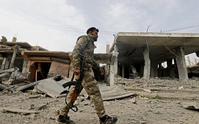 A fighter from the Syrian Democratic Forces (SDF) walks past a former Islamic State (IS) group jihadist alms tax center in Syria's eastern Deir Ezzor province on January 27, 2019 after the Kurdish-led and US-backed SDF retook the city from IS fighters. (DELIL SOULEIMAN / AFP)