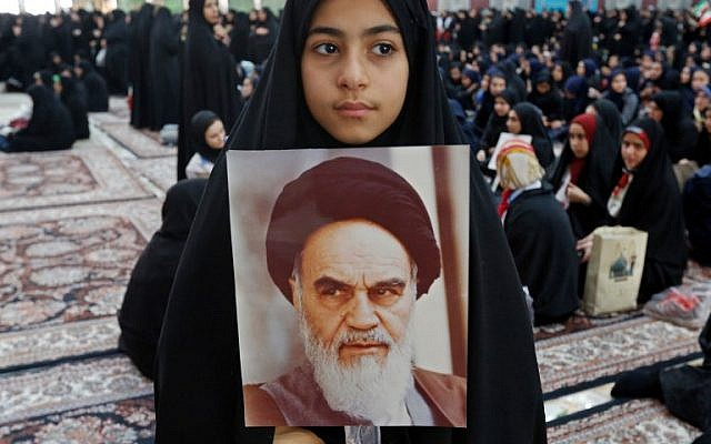 A girl holds a poster of Ayatollah Ruhollah Khomeini, the founder of the Islamic Republic, on the 40th anniversary of his return from exile from in Paris, at his mausoleum in southern Tehran, on February 1, 2019. (Stringer/AFP)