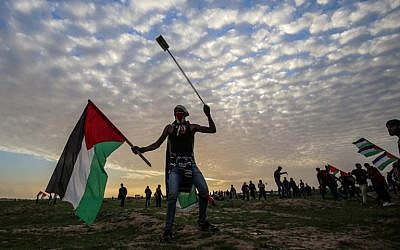 Illustrative: A Palestinian protester carries a national flag and a slingshot during a demonstration near the fence along the border with Israel, east of Gaza City, on February 1, 2019. (Said Khatib/AFP)