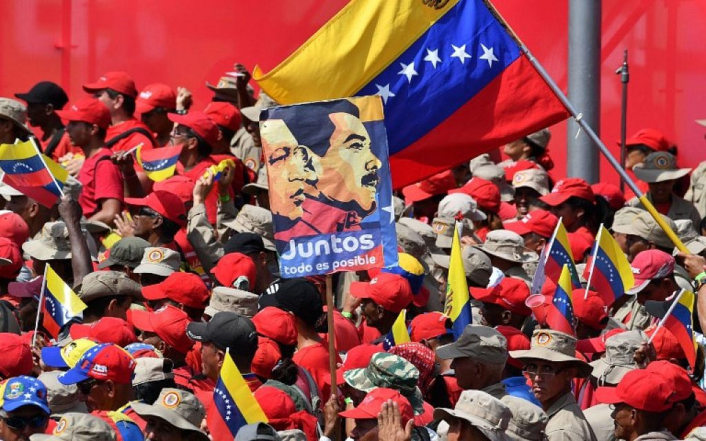 Supporters of Venezuelan President Nicolas Maduro gather to mark the 20th anniversary of the rise of power of the late Hugo Chavez, the leftist firebrand who installed a socialist government, in Caracas on February 2, 2019. - Protesters flowed into the streets of Caracas Saturday, with flags and placards, many to support opposition leader Juan Guaido's calls for democratic elections and others to back embattled President Nicolas Maduro. (Photo by Yuri CORTEZ / AFP)