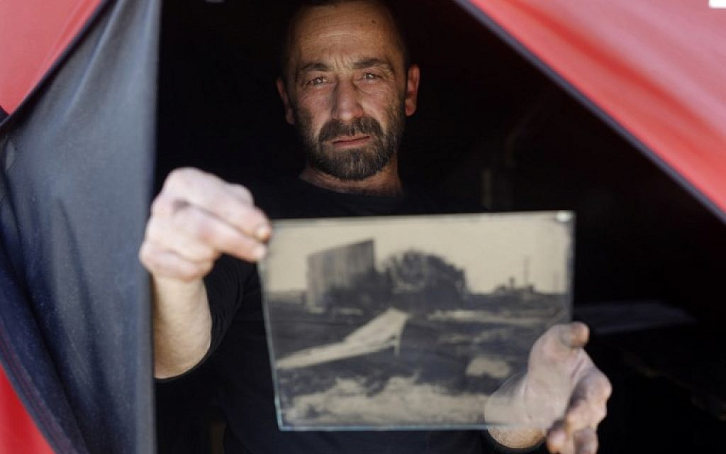 Edward Kaprov, an Israeli photographer, holds one of his images on a glass plate in his field darkroom, near Kibbutz Kissufim, overlooking the northern Gaza border, on February 5, 2019. (Menahem Kahana/AFP)