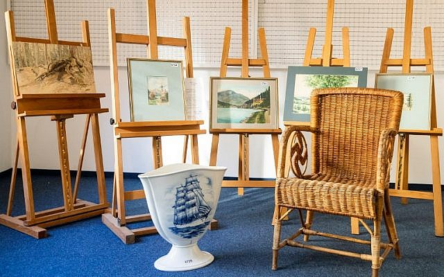 A picture taken on February 8, 2019, at the Weidler auction house in the southern German city of Nuremberg shows a wicker armchair, bearing a swastika, a vase and watercolors which are presumed to have belonged to late Nazi dictator Adolf Hitler. (Daniel Karmann/AFP)