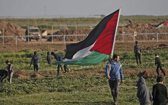 A Palestinian man carries the national flag during a demonstration near the fence along the border with Israel, east of Gaza City, on February 8, 2019. (Photo by MAHMUD HAMS / AFP)