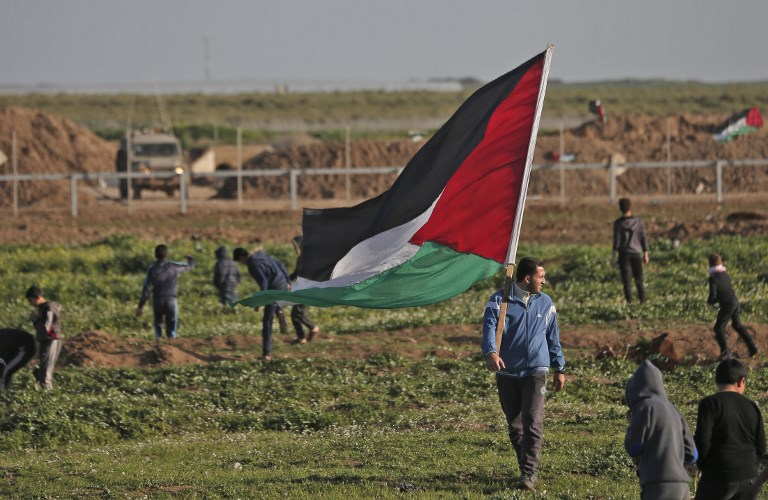 A Palestinian man carries the national flag during a demonstration near the fence along the border with Israel east of Gaza City